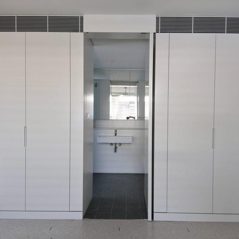 Wardrobe joinery with pivot door to ensuite bathroom